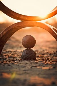 achieve balance in your work/life with Abhiyana Coaching: image of balanced stones at sunset