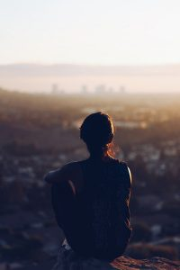 woman sat down and looking at the scenery in the distance